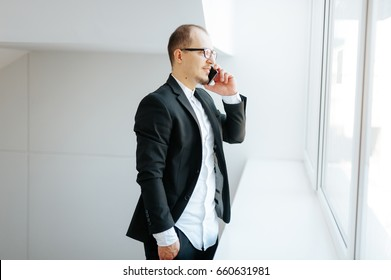 Young man talking on phone. Cheerful nice man talking on the phone. Portrait of young caucasian man talking on the phone