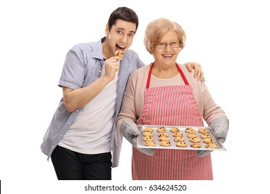 Young man tasting a freshly baked cookie by his grandmother isolated on white background