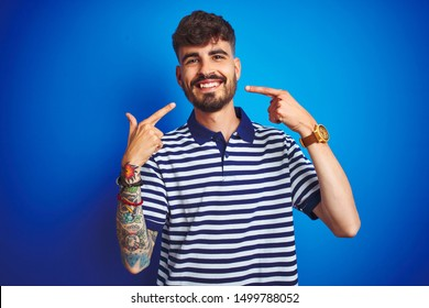 Young man with tattoo wearing striped polo standing over isolated blue background smiling cheerful showing and pointing with fingers teeth and mouth. Dental health concept.