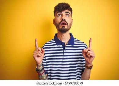 Young man with tattoo wearing striped polo standing over isolated yellow background amazed and surprised looking up and pointing with fingers and raised arms.