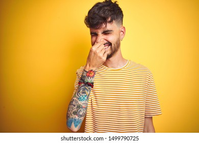 Young man with tattoo wearing striped t-shirt standing over isolated yellow background smelling something stinky and disgusting, intolerable smell, holding breath with fingers on nose. Bad smells