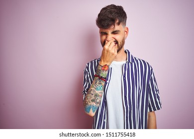 Young man with tattoo wearing striped shirt standing over isolated pink background smelling something stinky and disgusting, intolerable smell, holding breath with fingers on nose. Bad smells concept.