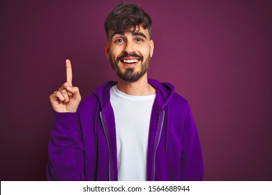 Young man with tattoo wearing striped polo standing over isolated yellow background pointing finger up with successful idea. Exited and happy. Number one.