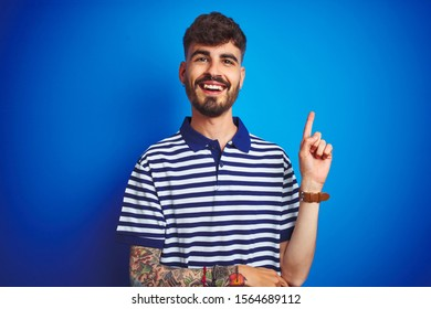 Young man with tattoo wearing striped polo standing over isolated blue background with a big smile on face, pointing with hand and finger to the side looking at the camera.