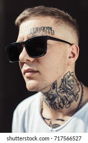 Young man with tattoos on face and neck posing in black sunglasses looking away.