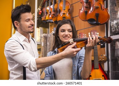 Young man is teaching girl to play the violin at the music store.