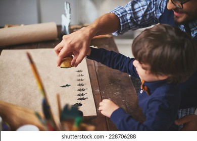 Young man teaching his son how to print on paper with help of potato and gouache