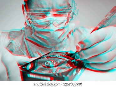 Young man technician wearing in protective glasses and mask repairs hard disk of computer. Image with anaglyph effect.