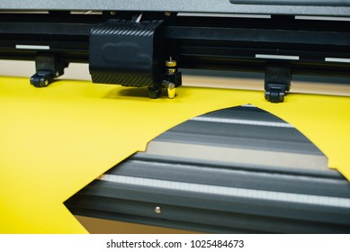 Young man technician working on plotter and cutter machine in printing centar
