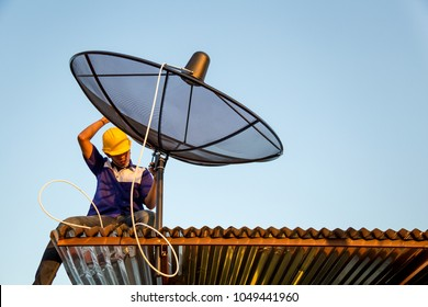 Young man technicians are installing satellite dish on roof