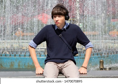 A young man, a teenager, sits at a fountain in a city park and listens to music in headphones. Youth culture.