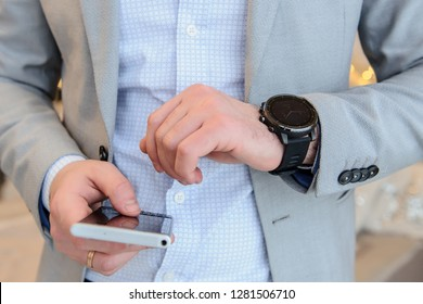 a young man with telephone in the right hand looking at his smartwatch