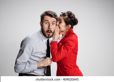 Young man telling gossips to his woman colleague at the office