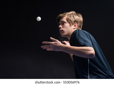 young man tennis player in play on black background