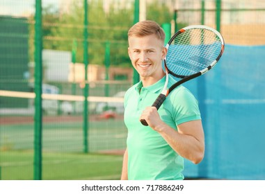 Young man with tennis racket on court