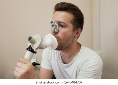 Young man testing breathing function by spirometry having health problem.