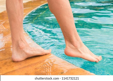 Young man testing the swimming pool temperature with his foot in the water