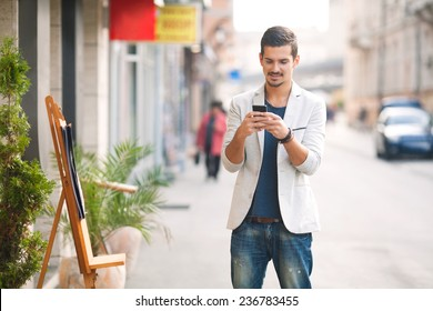Young man text messaging on the street