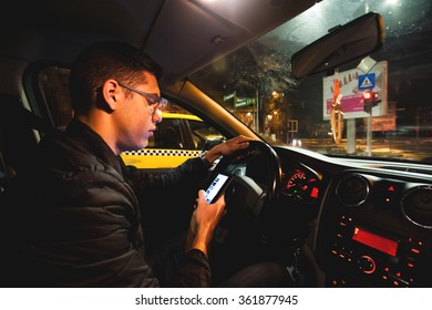 Young man texting and driving. Teenage driver on his cellphone while driving his car at night. Typing on the smartphone at the traffic lights. Dangerous driving concept.