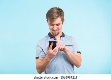 Young man texting message on smart phone isolated on blue background. Smiling guy holding smartphone and looking at it.