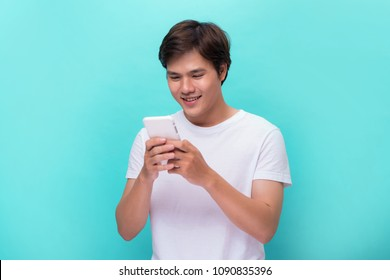 Young man texting message on smart phone isolated on blue background