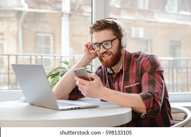 Young man texting message on smart phone while listening to music on earphones and enjoying free wireless internet connection at coffee shop