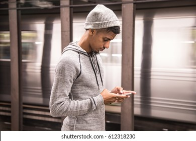 A young man texts while waiting for a NYC subway train. Shot during the Autumn of 2016