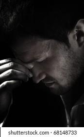 A young man that has an intense headache in dark.