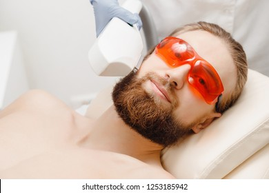 Young man with thick beard safety glasses demonstrates smoothness of skin laser hair removal on face and body in beauty salon