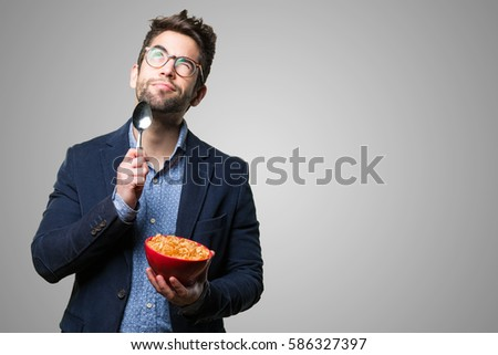 young man thinking holding corn flakes stock photo edit now