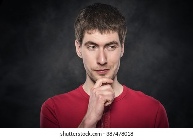 Young man thinking on a dark background.