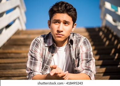 Young man thinking outside. Sitting on steps, looking into the distance, thinking