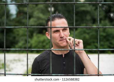 young man thinking while behid the metal bars