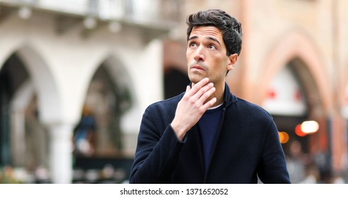 Young man in a thoughtful espression outdoor in the city