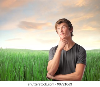 Young man with thoughtful expression on a green meadow