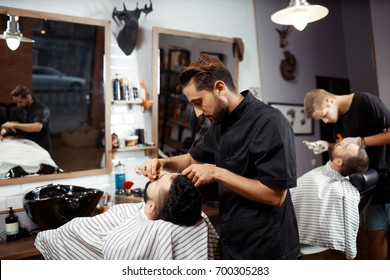 Young man threading eyebrows of young man in barbershop.