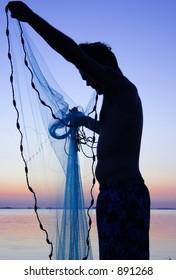 young man throwing cast-net at sunset over  Sarasota Bay