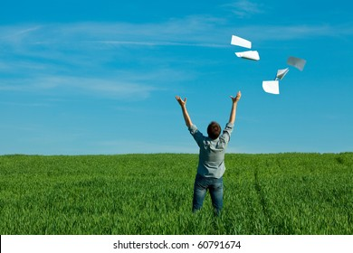 young man throwing a paper in the green field