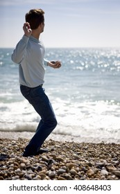 A young man throwing stones in the sea