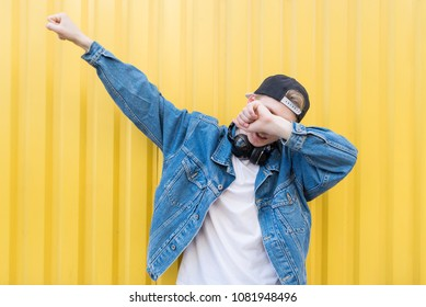 Young man throws dab on the background of a yellow wall.