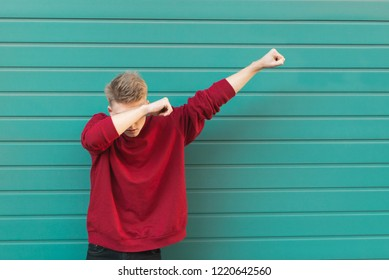 Young man throws dab on the background of a turquoise wall.