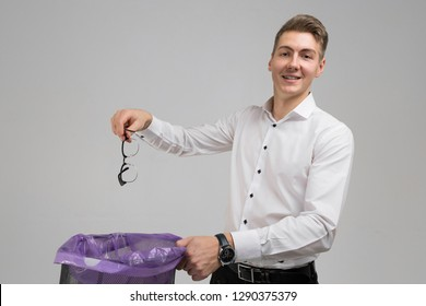 Young man throws glasses in trash isolated on white background