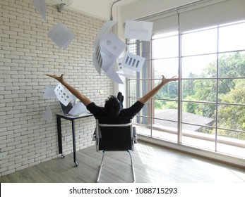Young man throws paper in the air.