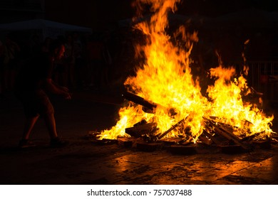 "A young man throws wood on a late-night bonfire on Saint John's Eve (""Nit de Sant Joan"" in Catalan), midsummer, being celebrated in Gràcia, Barcelona, Catalonia, Spain"