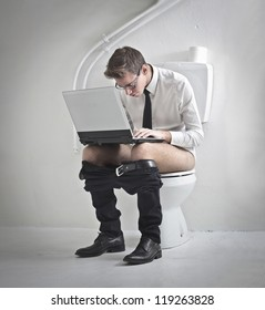 Young man in tie using a laptop computer on a toilet