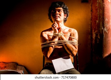 A young man with tied up and locked with rope and hold white paper for text input in the abandoned building, Infringement hostage and the anti Human Trafficking concept.