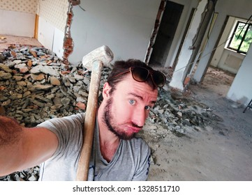 A young man with a tired, fatigued and perplexed expression takes a selfie holding a large hammer in his hands during the demolition of his old apartment to turn it into a new one. Renovation concept.