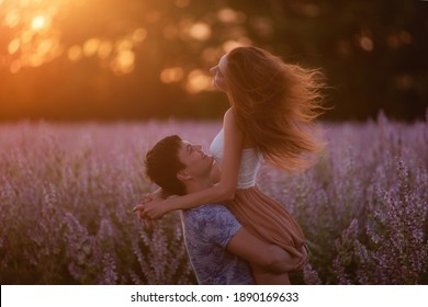 Young man took beautiful woman in his arms, whirls her around blooming purple sage field in the rays of the sunset. The girl's hair is flying in different directions. An offer of marriage. Copy space