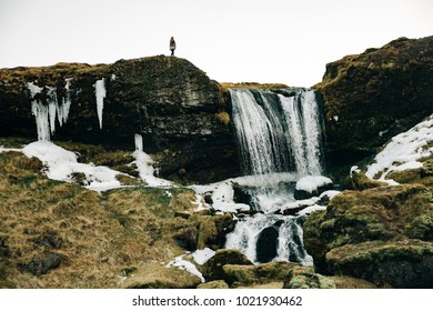 Young man at the top of Waterfall in Snaefellsnes peninsula