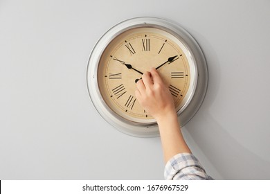 Young man touching arrows of clock on light wall - Shutterstock ID 1676967529
